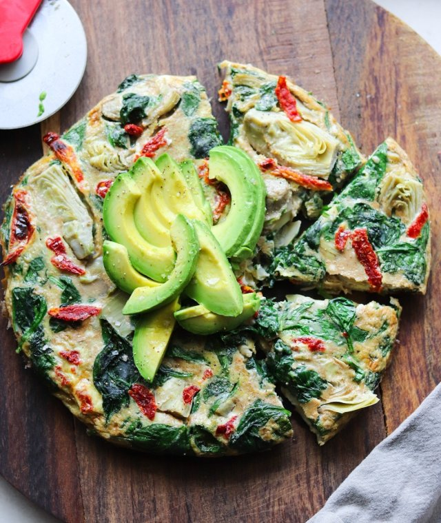 The finished frittata on a dark wooden cutting board, cut into slices and served with avocado.