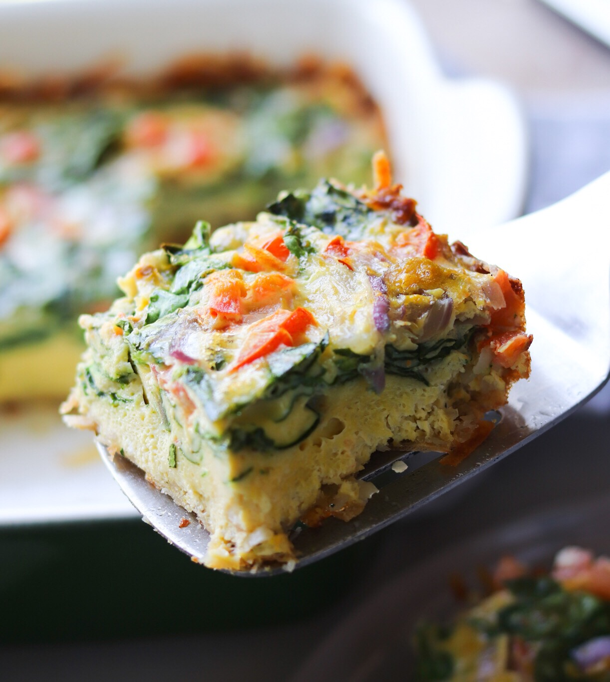 Whole30 Breakfast Casserole with hashbrown crust, side angle of an individual serving and sitting on a spatula.