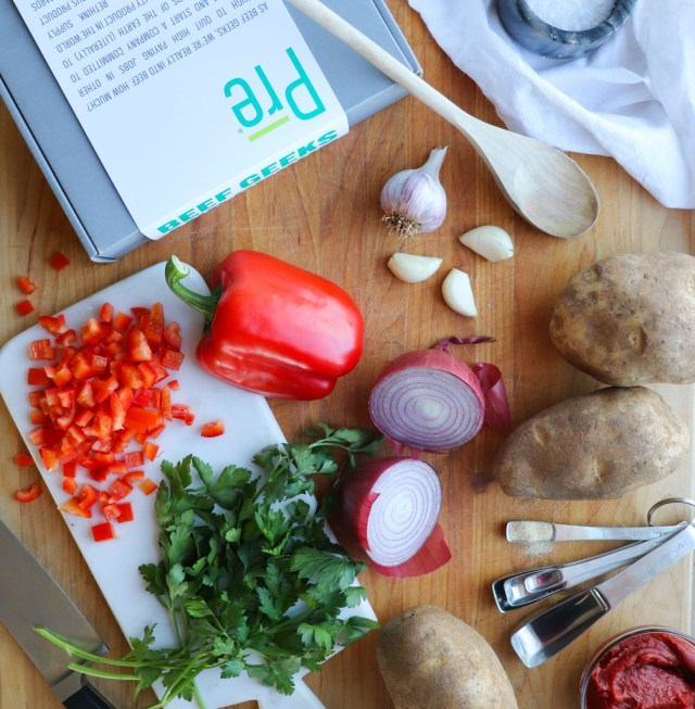 Whole30 and Paleo ingredients laid out on a cutting board, everything to make Sloppy Joes: whole potatoes, garlic, bell pepper, onion, tomato paste, and beef.