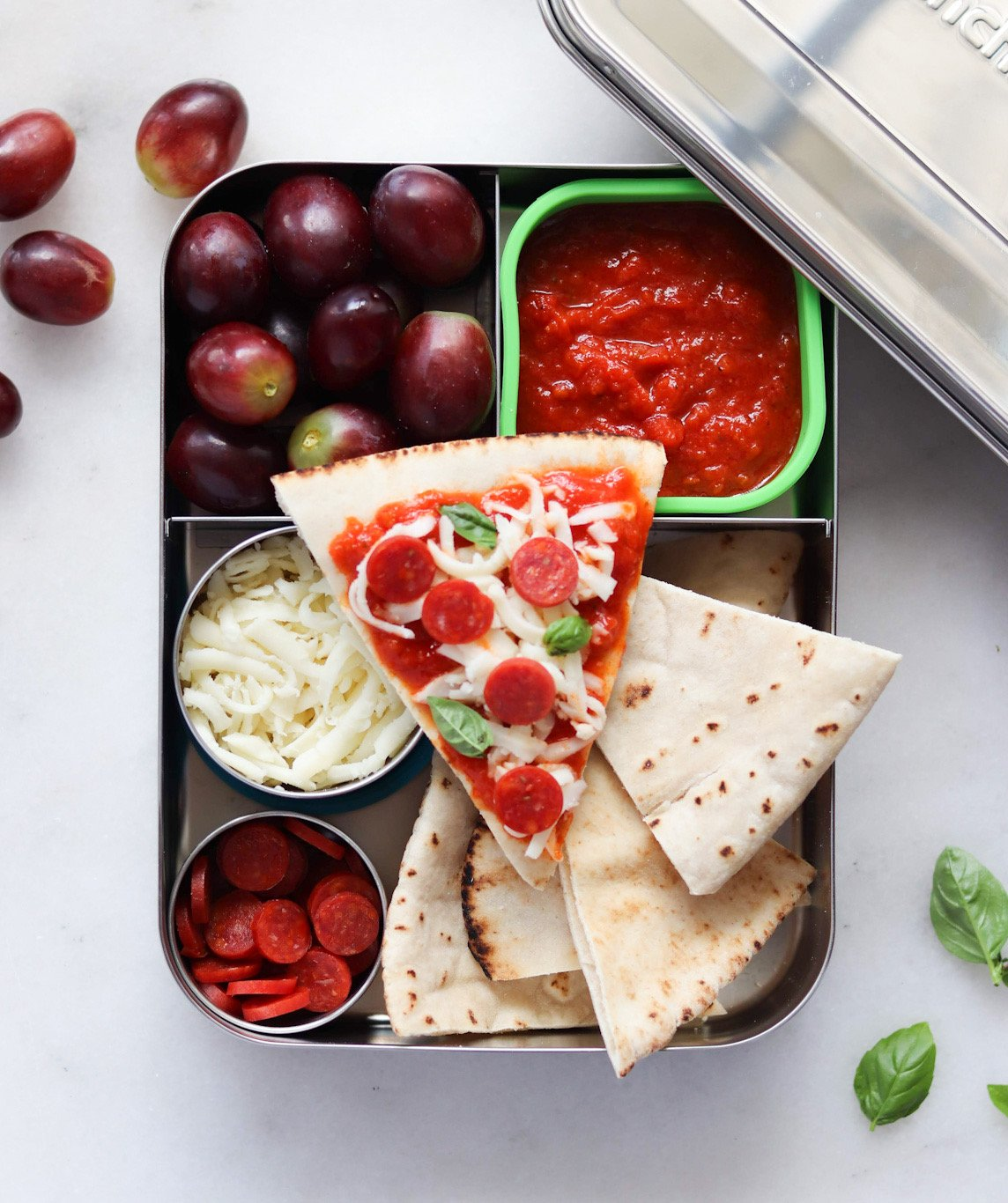 Top down of cut pitas, cheese, mini pepperoni and sauce inside a metal lunchbox.