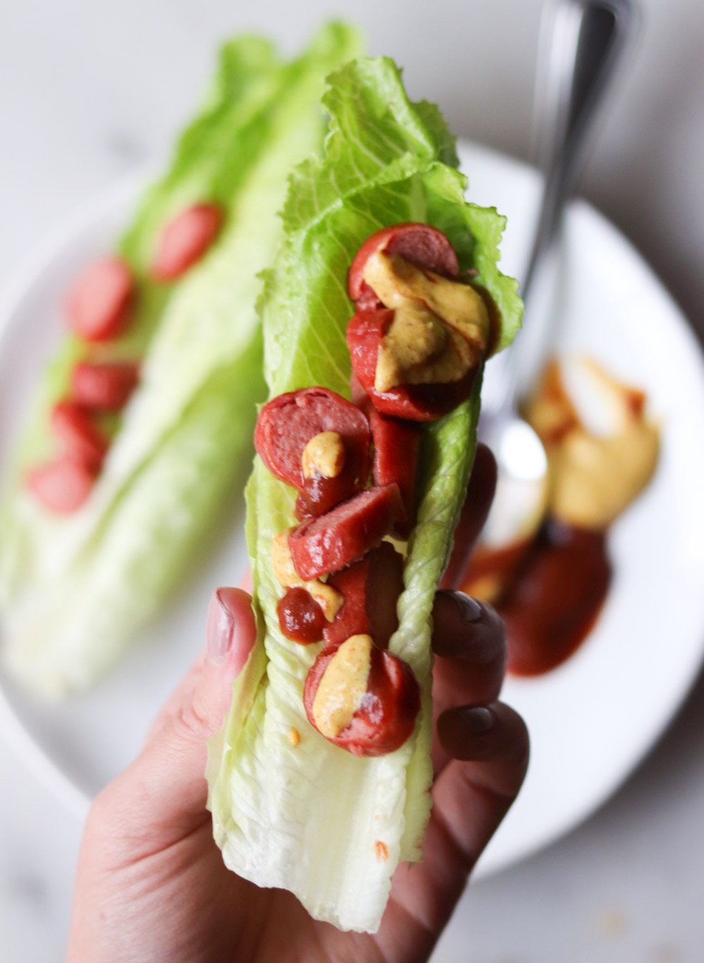 A hand holds a mini meal of small romaine lettuce wrap filled with half of a sliced Whole30 hot dog, ketchup, and mustard.