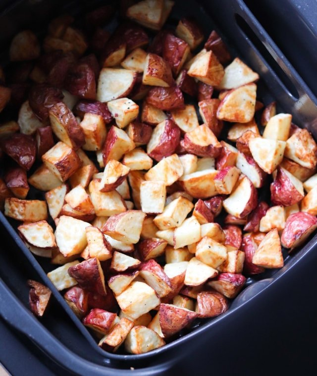 Finished roasted potatoes inside the air fryer basket.