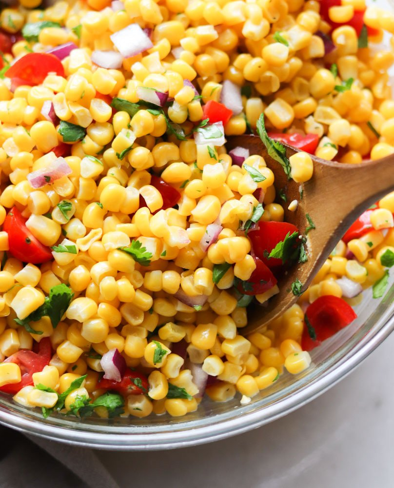 Close up side angle of the mixed chipotle corn salsa recipe in a glass bowl with a wooden serving spoon scooping some out.