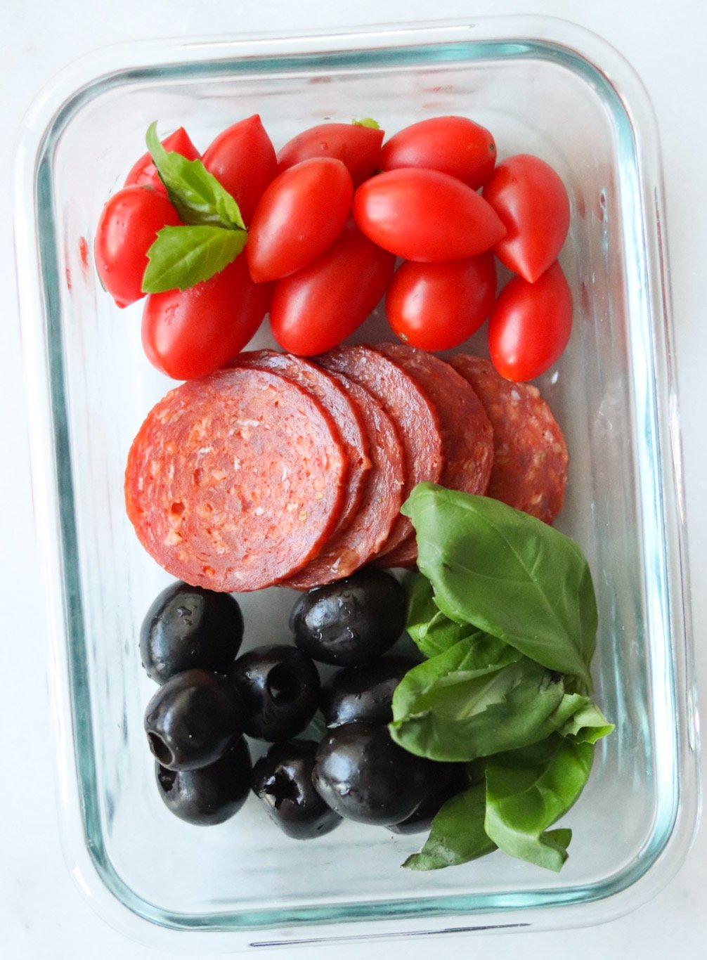 Whole30 mini meal in a glass container with pepperoni, olives, cherry tomatoes, and fresh basil.