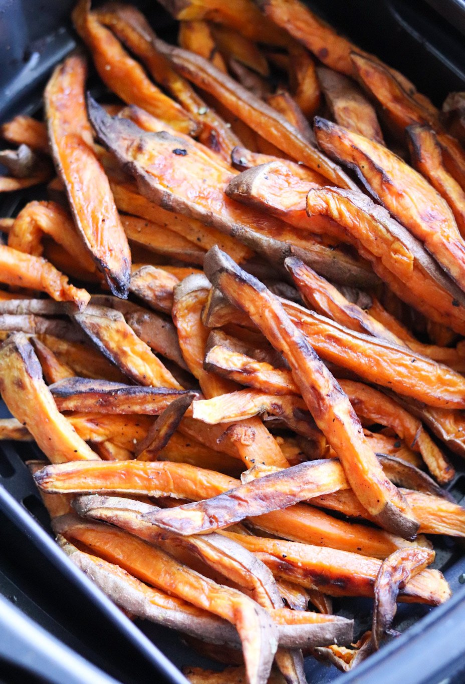 Close up of cooked crispy sweet potato fries in the air fryer basket.