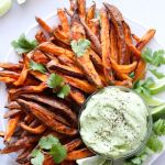"""Pinterest graphic with a close up of the cooked, plated sweet potato fries beside a small glass dish of aioli with the recipe title in large font: """"Air Fryer Sweet Potato Fries & Avocado Aioli."""""""