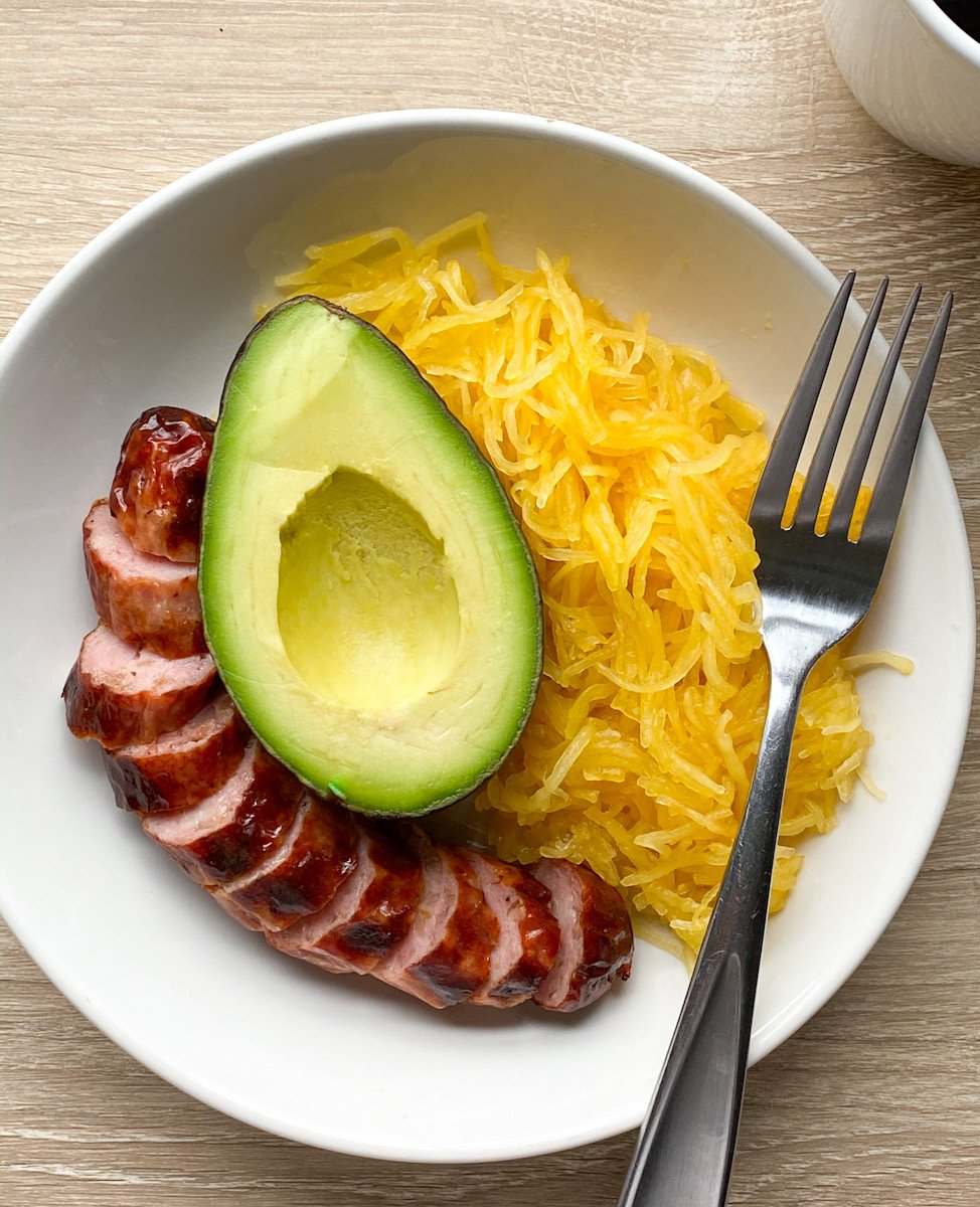 A breakfast bowl with a sliced cooked sausage, a half of an avocado, and spaghetti squash with a fork beside the bowl.