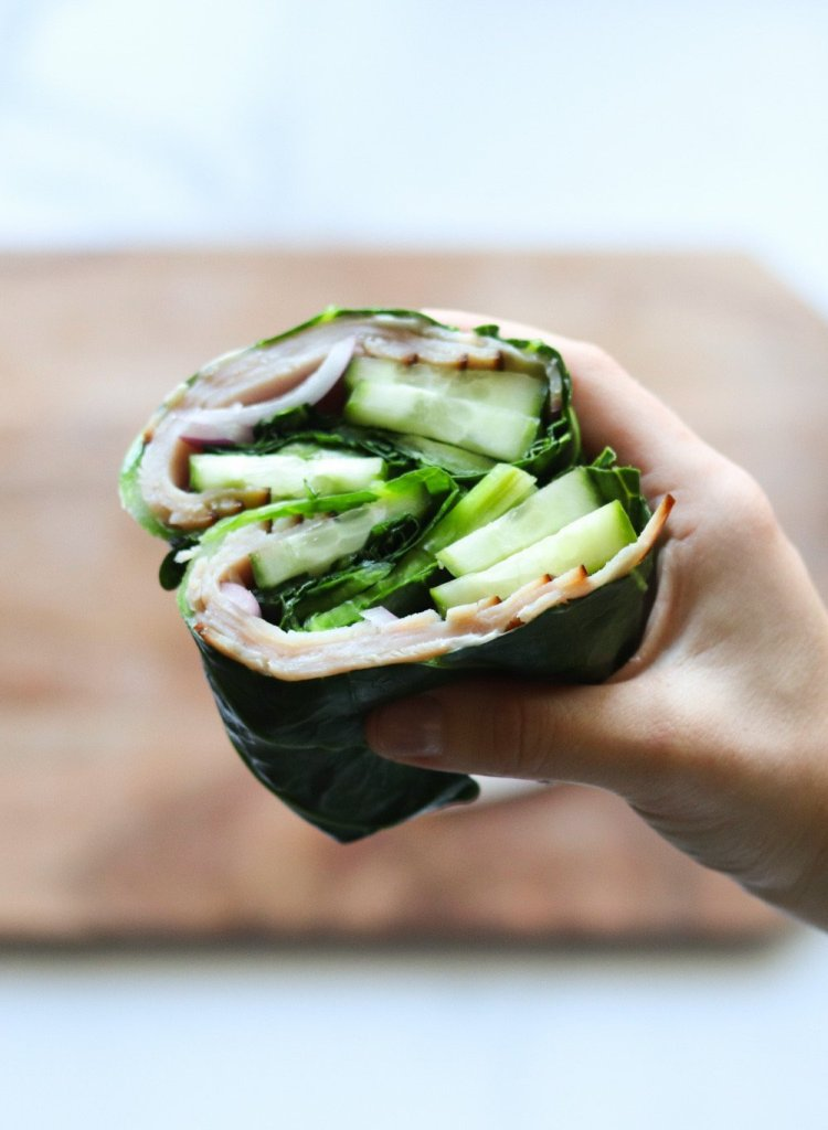 A hand holds a Keto and Paleo friendly wrap made with collard greens over a wooden cutting board.