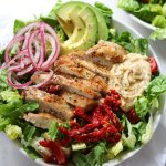 A white bowl filled with lettuce, avocado, sliced grilled chicken, sundried tomatoes, and pickled onions.