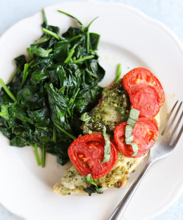 Close up of plated chicken covered in pesto and sliced tomatoes, served with sautéed spinach.