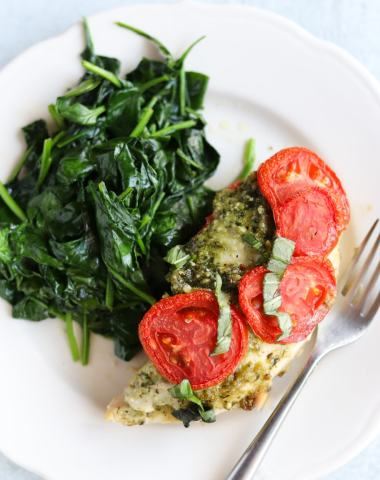 A white plate with baked chicken topped with pesto and tomatoes beside a side of sautéed spinach.