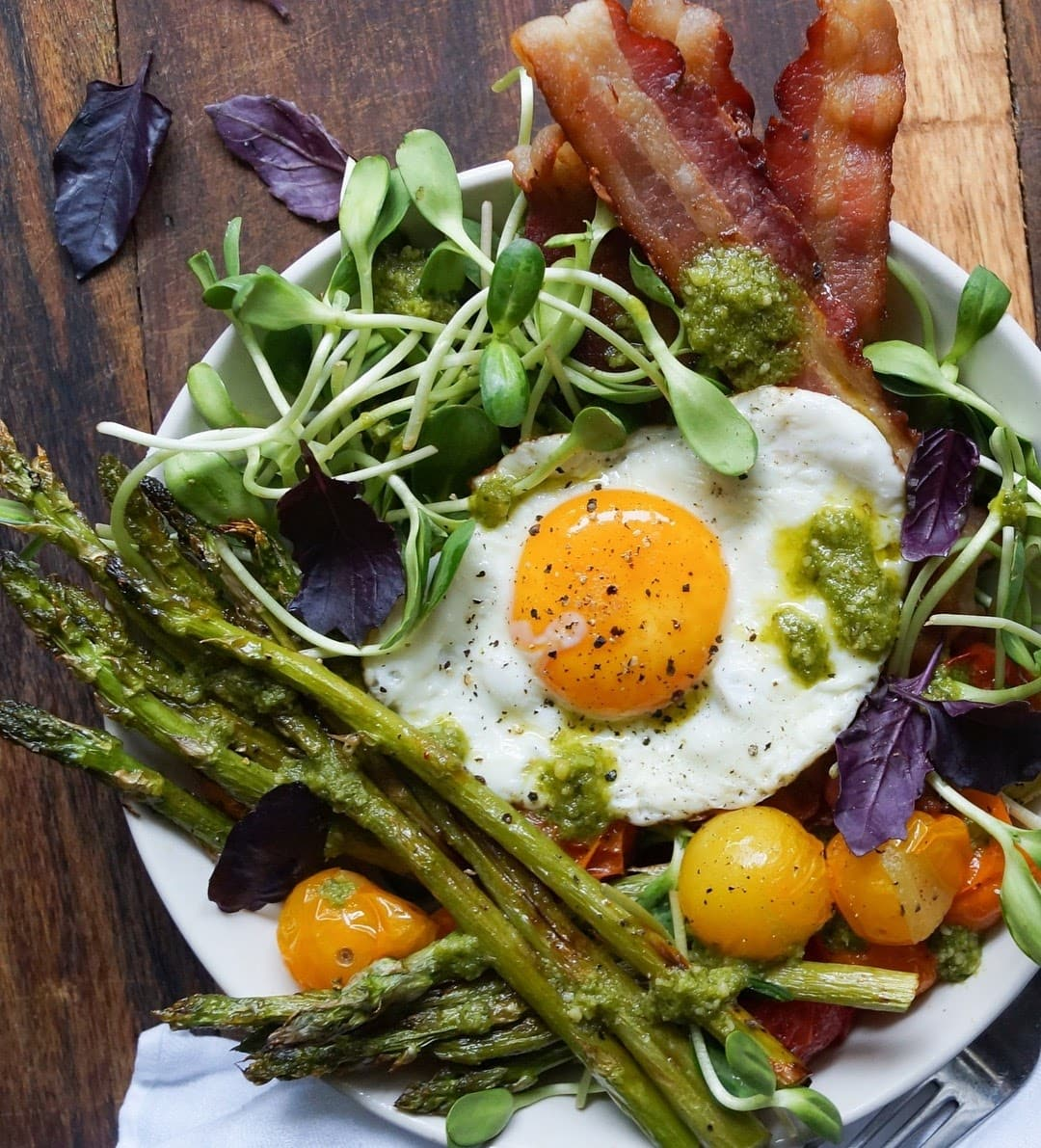 A breakfast bowl filled with roasted vegetables, bacon, a fried egg, and fresh herbs that's drizzled with pesto.