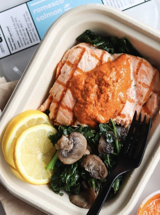 Snap Kitchen's Whole30 Romesco Salmon, served in the paper bowl with a plastic fork.