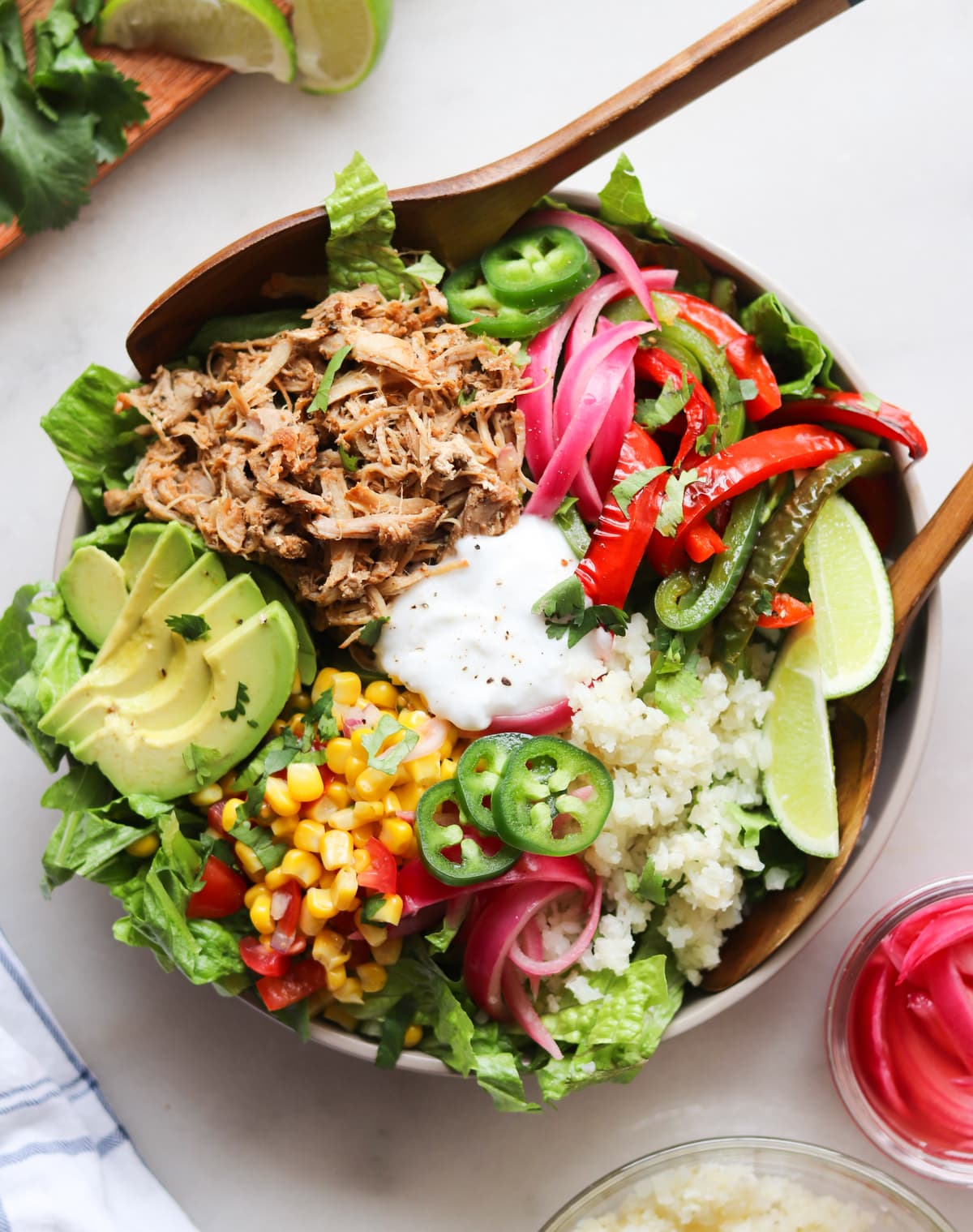 A large bowl on a white board filled with chopped romaine, carnitas pork, avocado, sour cream, cauliflower rice, and pickled onions.