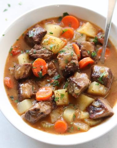 A white bowl filled with chunks of tender beef, sliced carrots and potatoes, and a creamy broth, all sprinkled with parsley and black pepper.