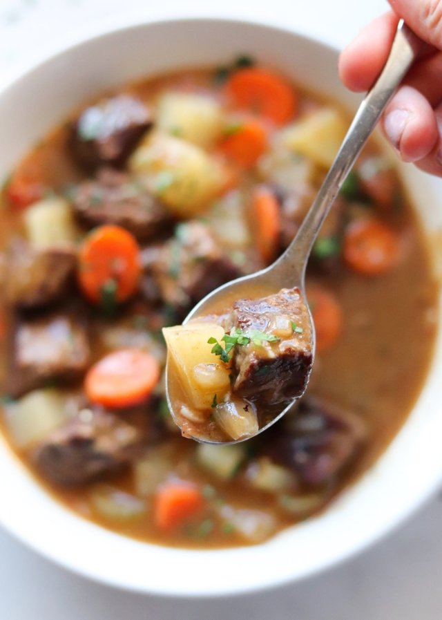 A close up of a spoonful of beef stew.