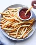 A gray plate filled with crispy French fries and a small ramekin of ketchup.