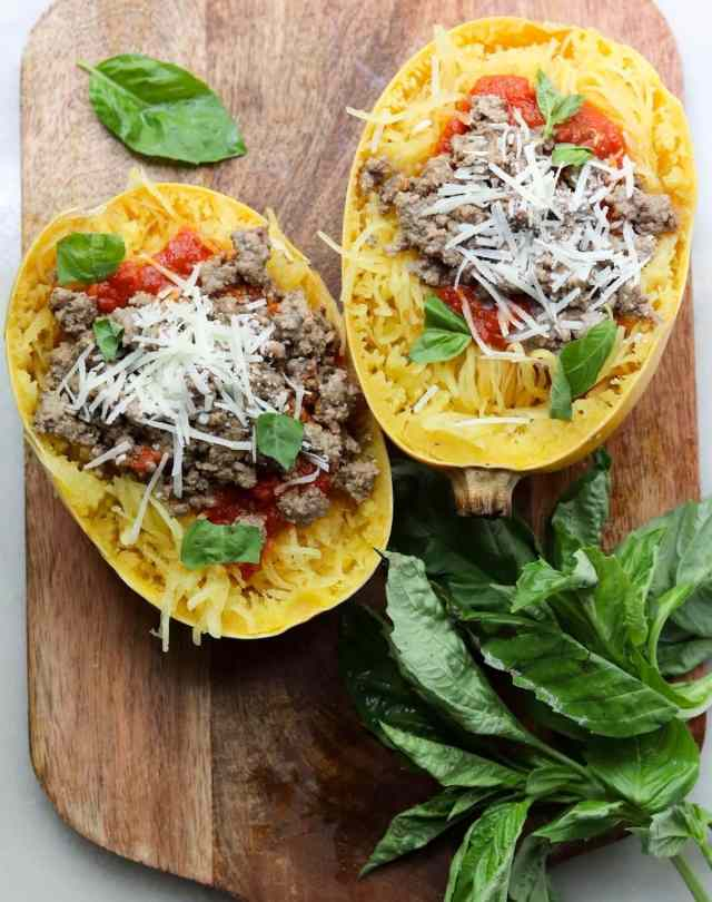 Two spaghetti squash halves filled with marinara, ground beef, parmesan cheese, and fresh basil.
