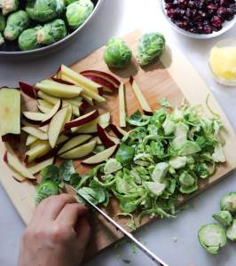 Brussels sprouts and apples being sliced on a wooden cutting board.
