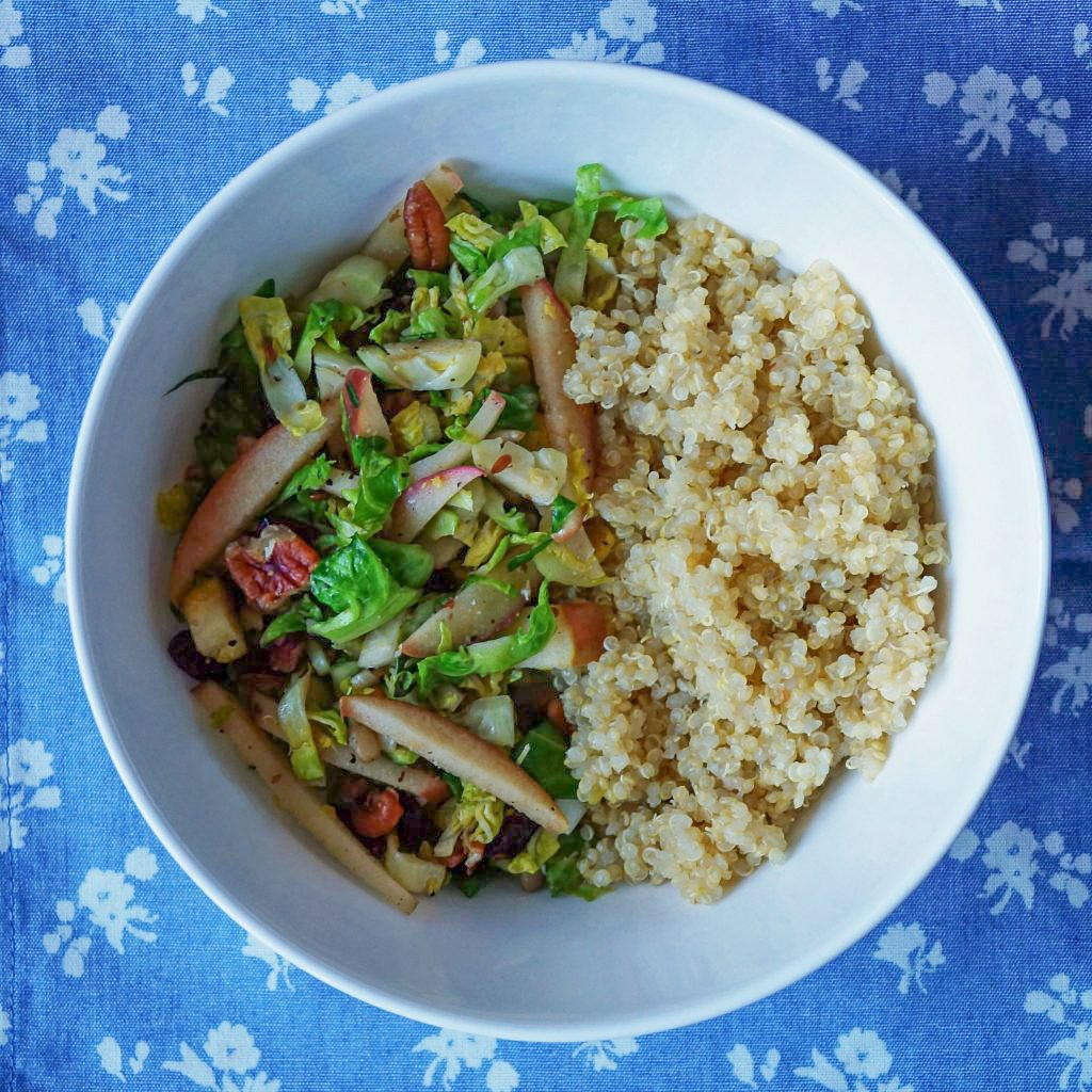 A white bowl filled halfway with quinoa and halfway with the cooked Brussels Sprouts Salad.