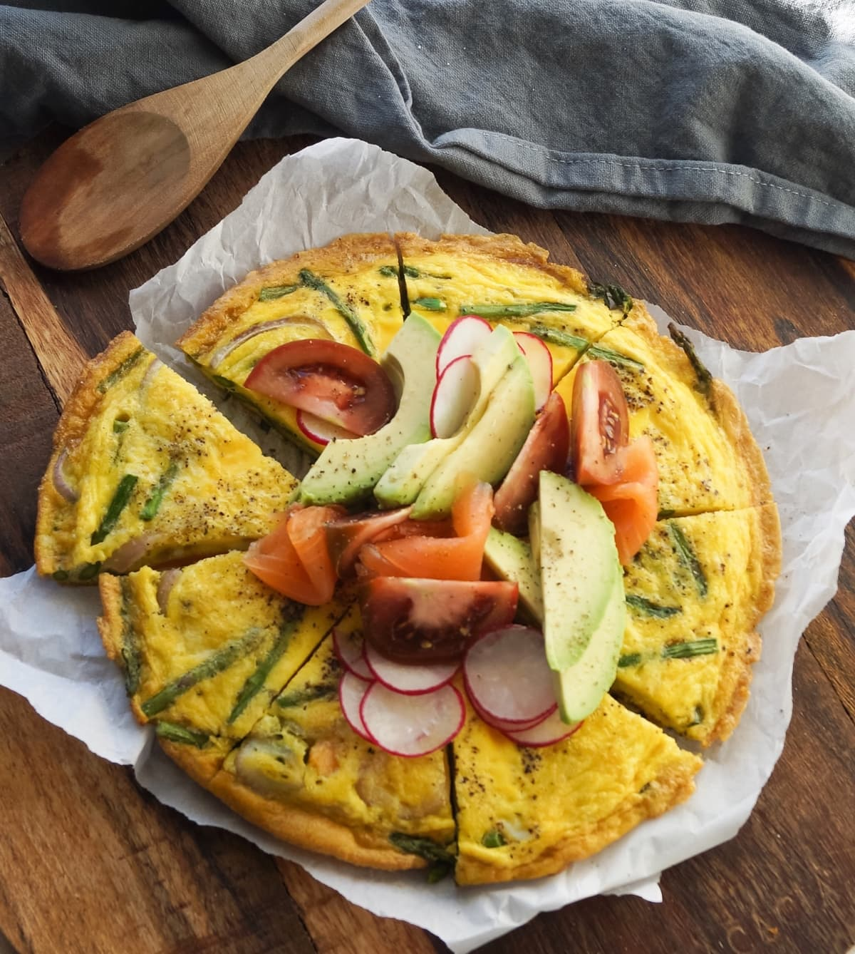 Top down of the finished frittata on a cutting board sliced into 8 pieces, topped with sliced avocado, tomato and radish.