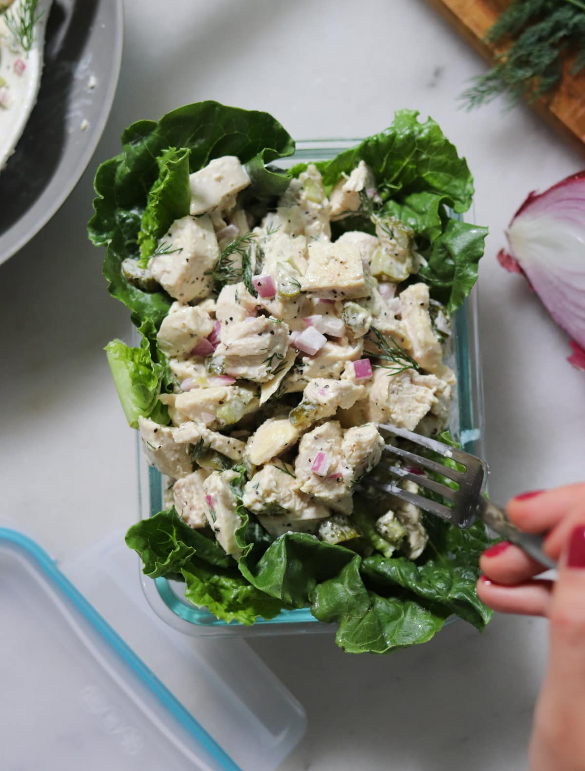 A small glass dish filled with romaine lettuce and topped with dill pickle chicken salad