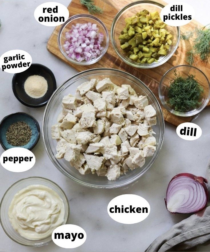 All ingredients in dishes laid out and labeled on a white marble board: Chicken, dill, pickles, onions, garlic powder, pepper, and mayo.