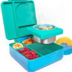 A green lunch box with compartments shown open with food packed inside.