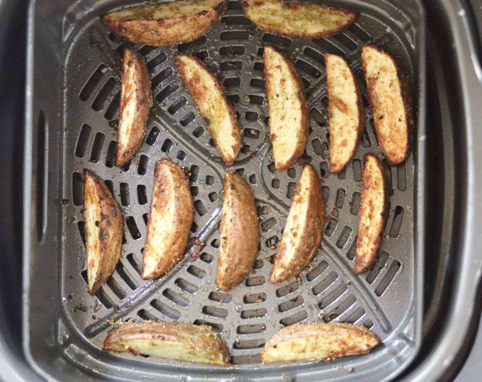 Cooked potato wedges inside the air fryer basket.