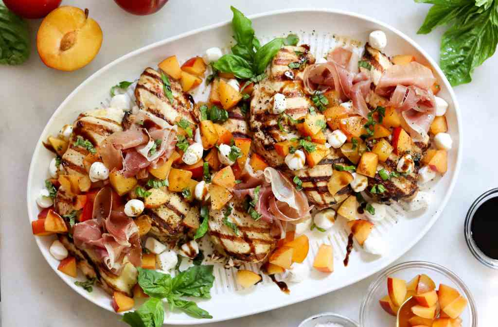 Top down of a large white platter on a white marble board filled with 5 grilled chicken breasts topped with diced apriums, mozzarella pears, sliced basil, and drizzled balsamic vinegar.