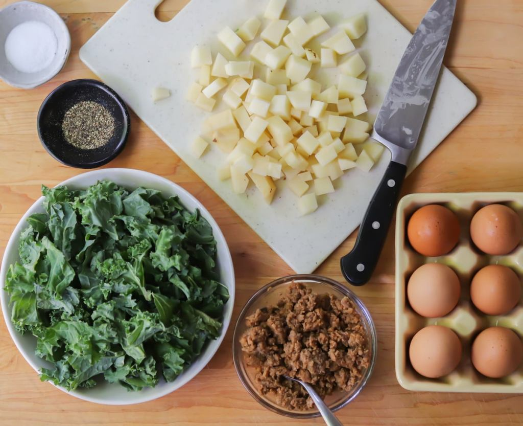 All of the recipe ingredients laid out on a wooden cutting board - diced potatoes, cooked chorizo sausage in a small bowl, chopped kale, and eggs.