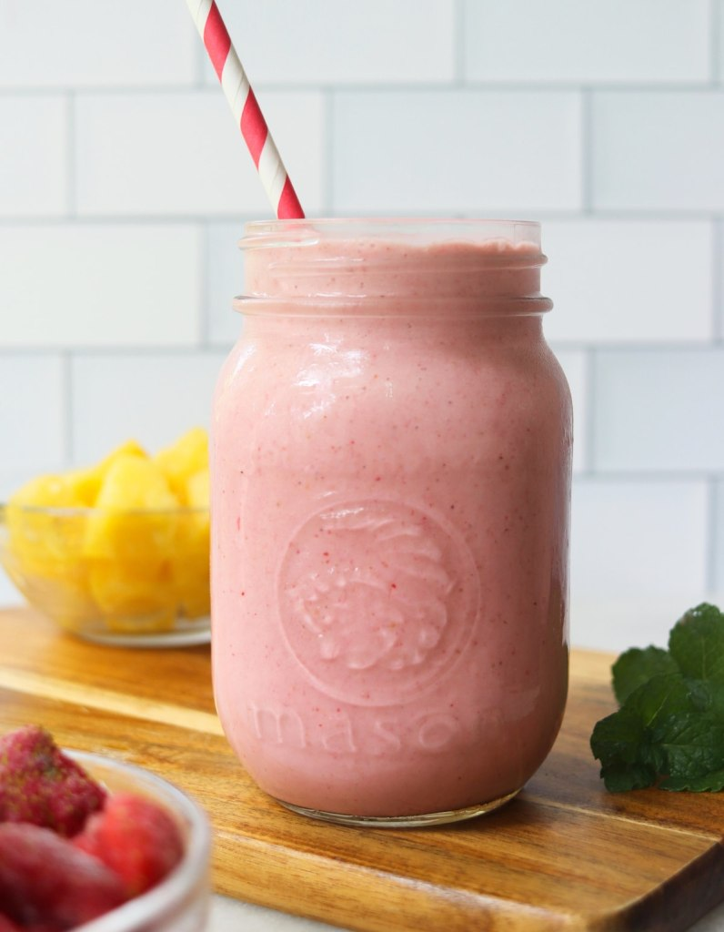 Side view of a mason jar filled with pink strawberry pineapple smoothie, served with a red straw.