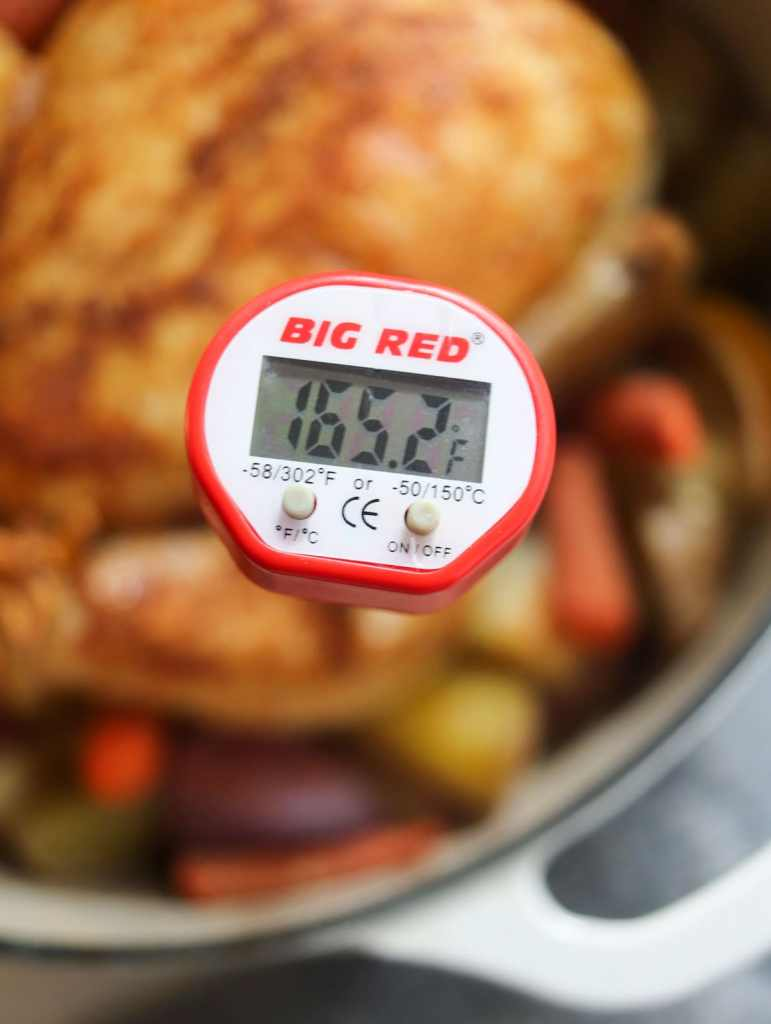 Close up of the meat thermometer inserted into the chicken thigh with the temperature 165.2.