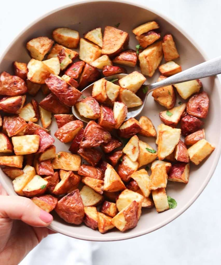 Close up of the finished potatoes in a bowl with a serving spoon.