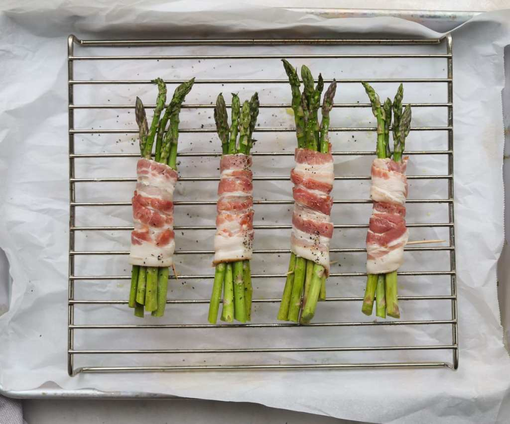 Four uncooked bundles of bacon wrapped asparagus on a baking rack over a parchment lined baking sheet.