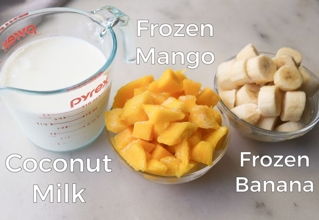 Labeled recipe ingredients on a white marble board: coconut milk in a measuring cup, a small glass dish filled with frozen mango, and a small glass dish filled with frozen banana.