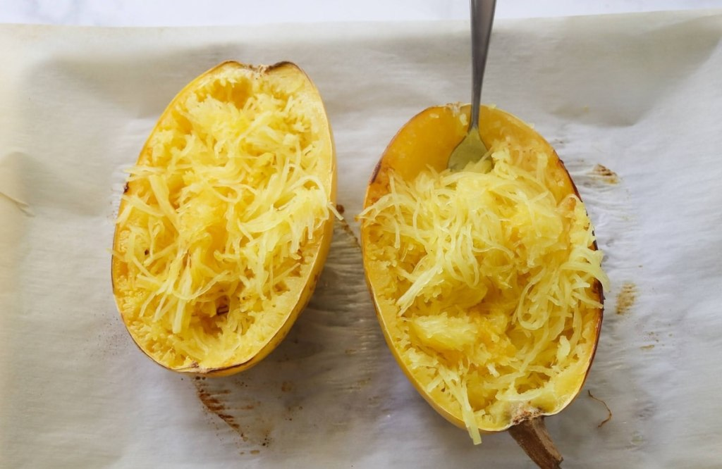 Two cooked spaghetti squash halves on a baking sheet.