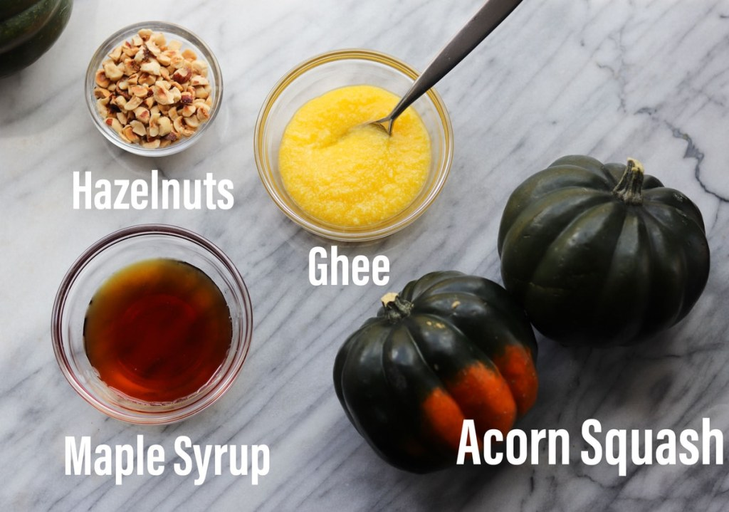 The recipe ingredients laid out on a marble board and labeled: hazelnuts, ghee, maple syrup, and acorn squash.