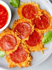 Close up top down of six crispy cheese rounds on a plate, each with a slice of pepperoni on top.