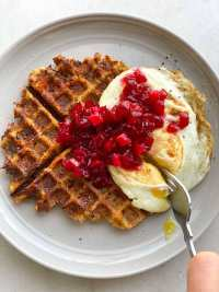 One crispy stuffing waffle on a gray plate topped with a fried egg and cranberry sauce.
