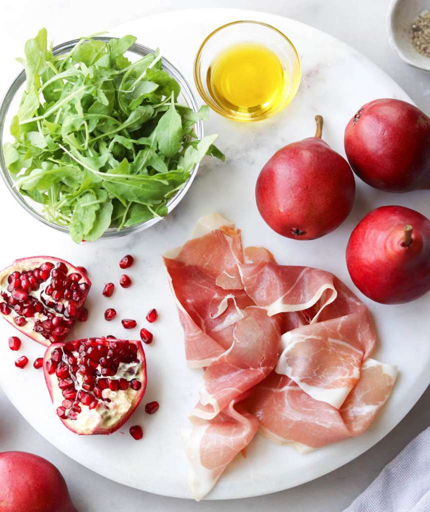 Recipe ingredients laid on a white marble board: arugula, oil, pomegranate, red pears, and prosciutto.