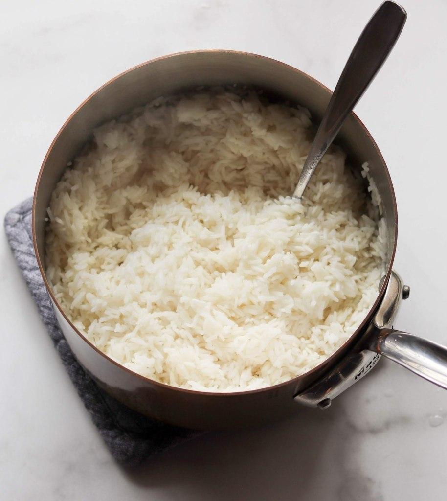 Close up top down of cooked rice in a copper pan.