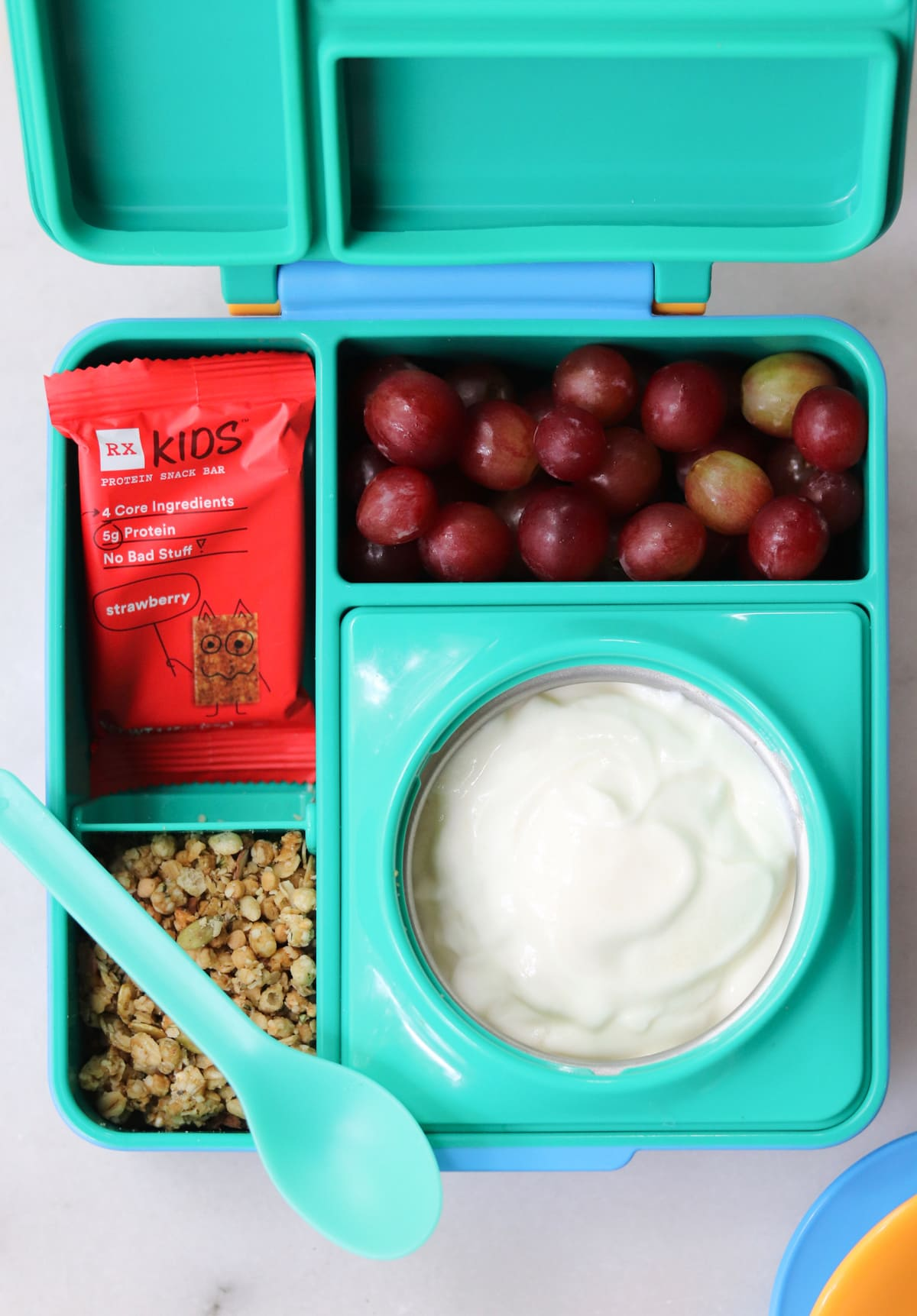 Close up of yogurt, granola, grapes, and a red kids rx bar inside a green lunch box.