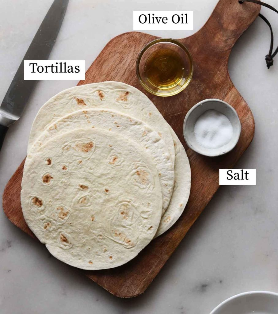 The recipe ingredients laid out and labeled on a cutting board: tortillas, olive oil, and salt.