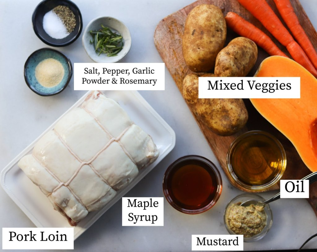 The recipe ingredients labeled on a white marble board: seasonings, pork loin, maple syrup, mustard, oil, and vegetables.