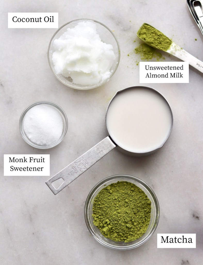 The ingredients in individual dishes on a white marble board, labeled: coconut oil, unsweetened almond milk, monk fruit sweetener, and matcha.
