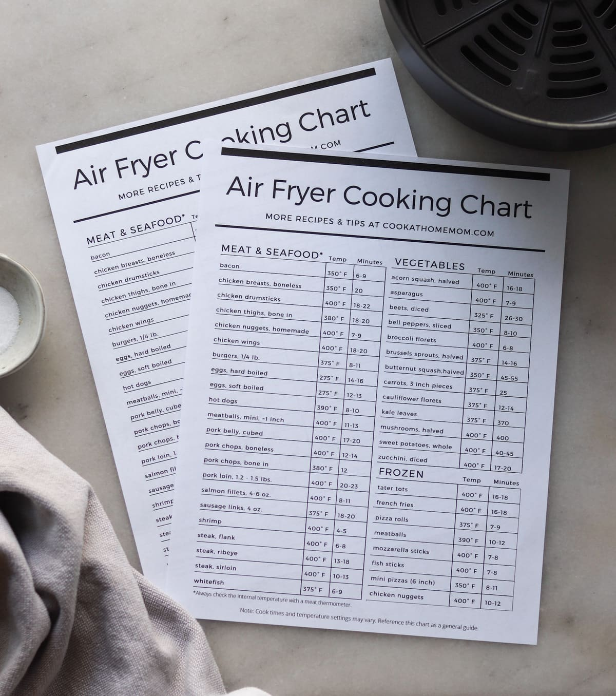Two printed air fryer cooking charts on a white marble board beside an air fryer basket and kitchen towel.