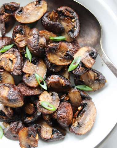 A white bowl filled with crispy air fryer mushrooms.