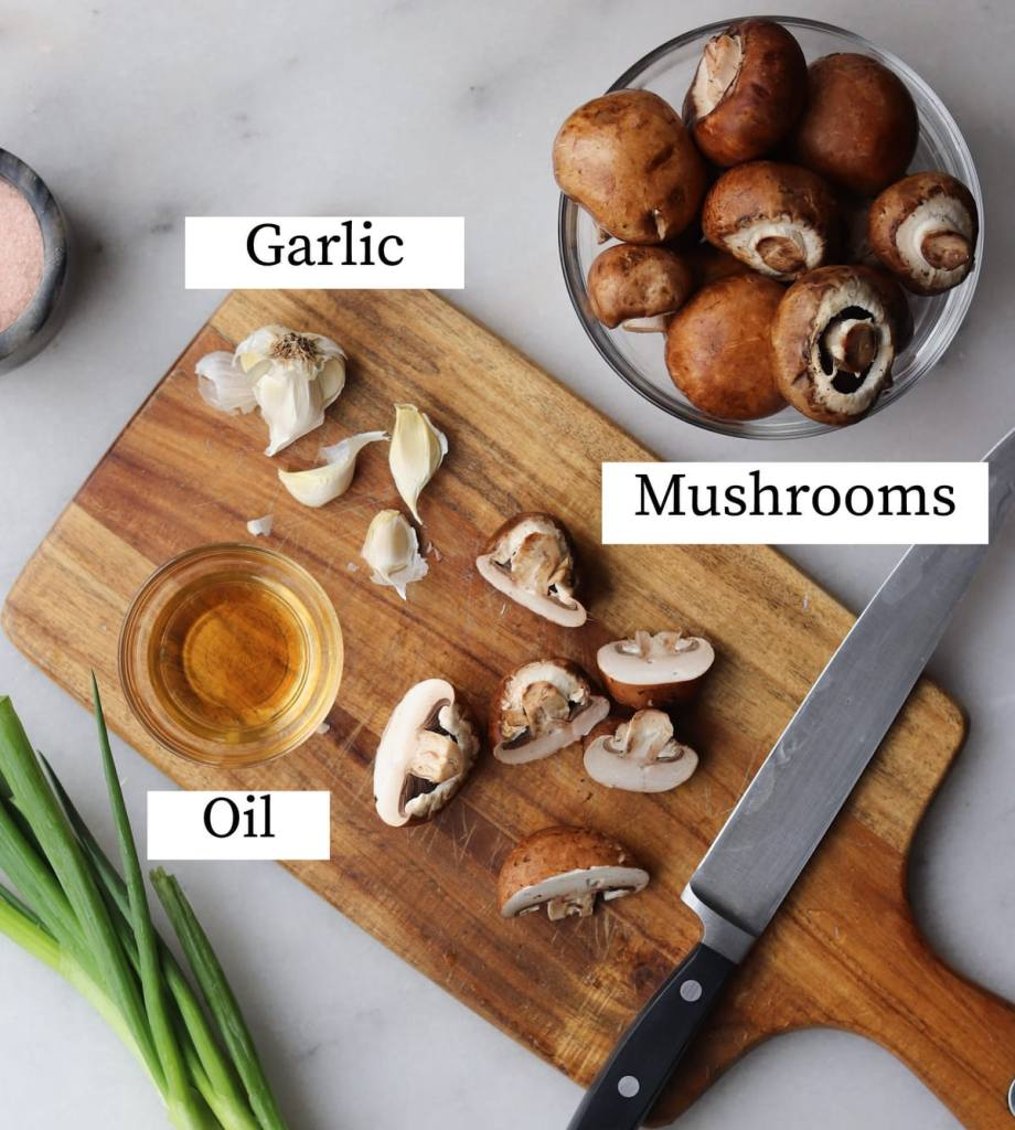 The recipe ingredients labeled on a cutting board: Garlic, mushrooms, and oil.