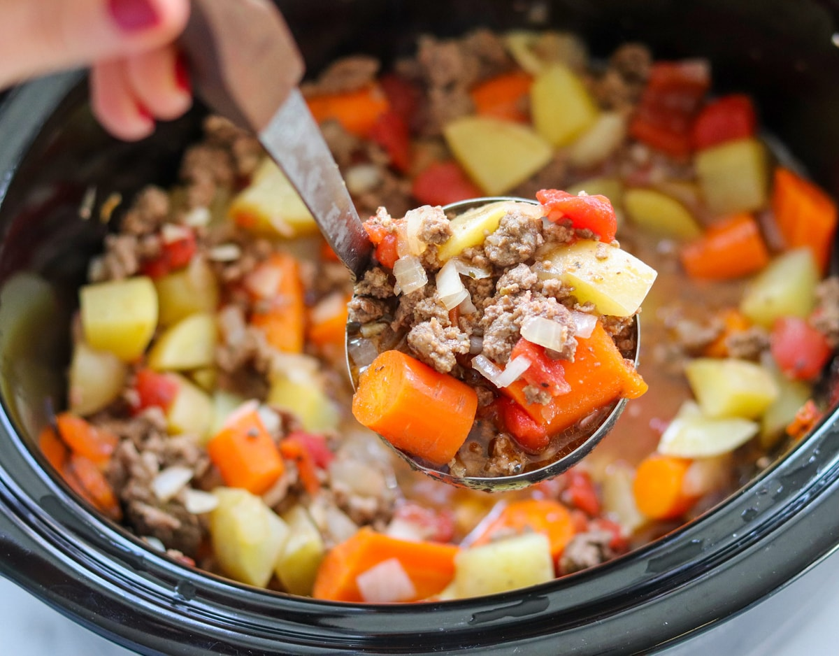 A hand ladling out a scoop of the stew from the slow cooker.